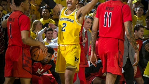 Michigan guard Jordan Poole (2) celebrates between Maryland guards Anthony Cowan Jr. (1) and Jared Nickens (11) in the second half of an NCAA college basketball game at Crisler Center in Ann Arbor, Mich., Monday, Jan. 15, 2018. (AP Photo/Tony Ding)