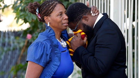 FILE - In this Dec. 12, 2016 file photo, a woman comforts an unidentified mourner as he cries into a scarf with University of Southern California colors before funeral services for former NFL football player Joe McKnight at the New Home Family Worship Center in New Orleans. The trial in a road-rage shooting that left McKnight dead was set to begin with jury selection Tuesday, Jan. 16, 2018, in a New Orleans suburb. McKnight was shot to death by Ronald Gasser in the December 16 shooting. (AP Photo/Gerald Herbert, File)