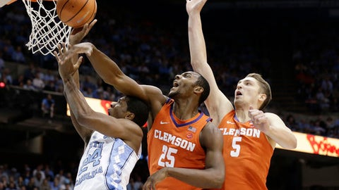North Carolina's Kenny Williams (24) drives to the basket against Clemson's Aamir Simms (25) and Mark Donnal (5) during the first half of an NCAA college basketball game in Chapel Hill, N.C., Tuesday, Jan. 16, 2018. (AP Photo/Gerry Broome)