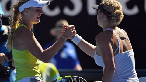 Denmark's Caroline Wozniacki, left, is celebrated by Croatia's Jana Fett as she won their second round match at the Australian Open tennis championships in Melbourne, Australia, Wednesday, Jan. 17, 2018. (AP Photo/Andy Brownbill)