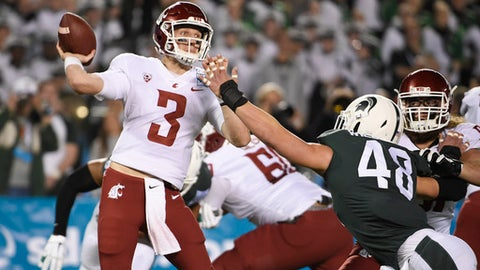 FILE - In this Dec. 28, 2017, file photo, Washington State quarterback Tyler Hilinski throws under pressure from Michigan State defensive end Kenny Willekes (48) during the first half of the Holiday Bowl NCAA college football game in San Diego. Hilinski has died from an apparent self-inflicted gunshot wound. The 21-year-old Hilinski was discovered in his apartment after he didn't show up for practice Tuesday, Jan. 16, 2018. (AP Photo/Denis Poroy, File)