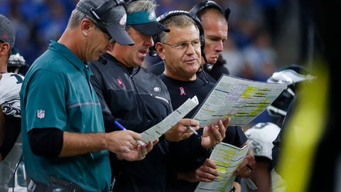FILE - In this Oct. 9, 2016, file photo, from left, Philadelphia Eagles offensive coordinator, Frank Reich, head coach Doug Pederson, offensive line coach Jeff Stoutland and tight ends coach Justin Peelle talk during an NFL football game against the Detroit Lions in Detroit. Whether it's a deep pass into the wind on the first play from scrimmage, going for it on fourth down or trying new plays, the Eagles' offensive coaching staff is aggressive no matter the conditions. (AP Photo/Paul Sancya, File)