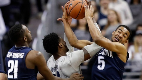 Georgetown forward Marcus Derrickson (24) and Villanova guard Phil Booth (5) go for the rebound with Villanova forward Dhamir Cosby-Roundtree (21) nearby, during the first half of an NCAA college basketball game, Wednesday, Jan. 17, 2018, in Washington. (AP Photo/Alex Brandon)