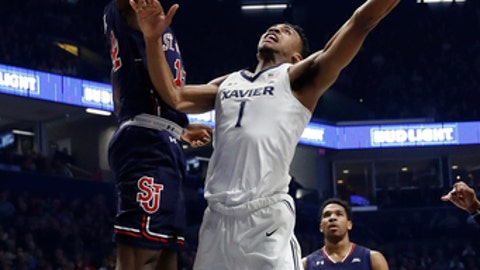 Xavier's Paul Scruggs (1) shoots against St. John's Kassoum Yakwe (14) in the first half of an NCAA college basketball game, Wednesday, Jan. 17, 2018, in Cincinnati. (AP Photo/John Minchillo)