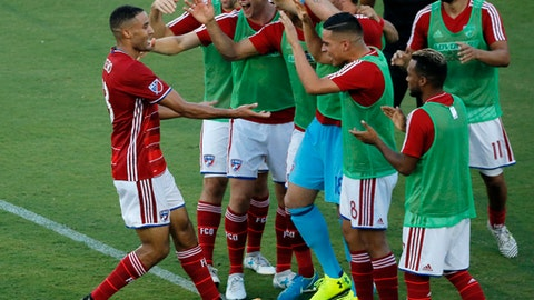 FILE - In this Aug. 23, 2017, file photo, FC Dallas forward Tesho Akindele, left, celebrates with teammates after scoring a goal against the Houston Dynamo during the first half of an MLS soccer match, in Frisco, Texas. Major League Soccer has extended a partnership with Southern New Hampshire University that helps the league's players and employees to pursue their college degrees. Akindele completed his bachelor's degree and will soon begin work toward a master's in finance. On Thursday, Jan. 18, 2018, the league announced that it is extending the partnership _ which started in 2015 _ through 2020.(AP Photo/Tony Gutierrez)