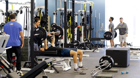 In this Tuesday, Dec. 12, 2017, photo, tennis players work out in the gym at the USTA National Campus in Orlando, Fla.  It's where dozens of professional players from the country go through preseason preparations. (AP Photo/John Raoux)