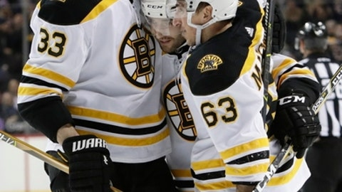Boston Bruins' Zdeno Chara (33) and Brad Marchand (63) celebrate with teammate Patrice Bergeron after he scored his third goal of the game during the third period of an NHL hockey game against the New York Islanders, Thursday, Jan. 18, 2018, in New York. (AP Photo/Frank Franklin II)