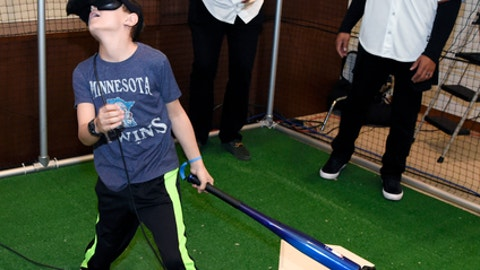 Minnesota Twins' Michael Pineda and Ehire Adrianza react as a fan misses a home run while playing a virtual reality game during day two at the baseball team's TwinsFest, Saturday, Jan. 20, 2018 in Minneapolis. (AP Photo/Hannah Foslien)