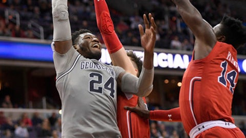 Georgetown forward Marcus Derrickson (24) shoots against St. John's forward Amar Alibegovic, center, and forward Kassoum Yakwe (14) during the second overtime of an NCAA college basketball game, Saturday, Jan. 20, 2018, in Washington. Georgetown won 93-89 in double overtime. (AP Photo/Nick Wass)