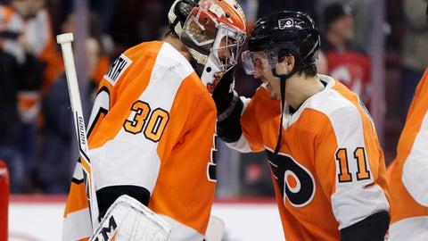 Philadelphia Flyers' Michal Neuvirth, left, and Travis Konecny celebrate after an NHL hockey game against the New Jersey Devils, Saturday, Jan. 20, 2018, in Philadelphia. Philadelphia won 3-1. (AP Photo/Matt Slocum)