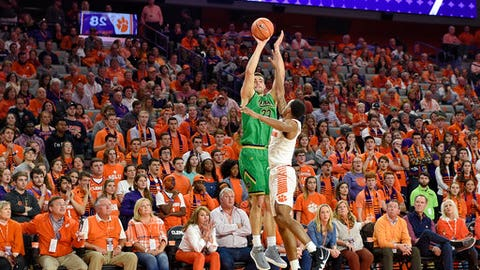 Notre Dame's Martinas Geben (23) shoots a three-pointer while defended by Clemson's Marcquise Reed during the first half of an NCAA college basketball game Saturday, Jan. 20, 2018, in Clemson, S.C. (AP Photo/Richard Shiro)