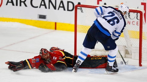 Winnipeg Jets' Blake Wheeler (26) scores on Calgary Flames goalie Mike Smith during a shoot out in their NHL hockey game in Calgary, Alberta, Saturday, Jan. 20, 2018. (Todd Korol/The Canadian Press via AP)