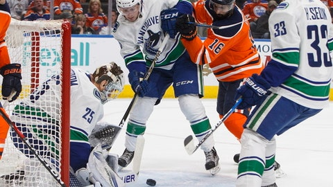 Vancouver Canucks goalie Jacob Markstrom (25) makes a save as teammate Jake Virtanen (18) and Edmonton Oilers' Jujhar Khaira (16) battle in front during the second period of an NHL hockey game Saturday, Jan. 20, 2018, in Edmonton, Alberta. (Jason Franson/The Canadian Press via AP)
