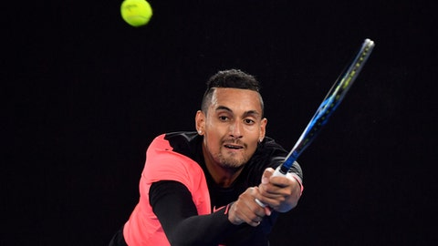 Australia's Nick Kyrgios makes a backhand return to Bulgaria's Grigor Dimitrov during their fourth round match at the Australian Open tennis championships in Melbourne, Australia Sunday, Jan. 21, 2018. (AP Photo/Andy Brownbill)