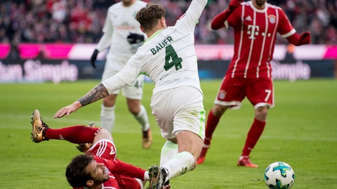 Bayern Munich's Juan Bernat, left, and Bremen's Robert Bauer challenge for the ball during the German first division Bundesliga soccer match between Bayern Munich and Werder Bremen in the Allianz Arena in Munich, Germany, Sunday, Jan. 21, 2018. (Sven Hoppe/dpa via AP) via AP)