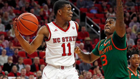 North Carolina State's Markell Johnson (11) looks to pass the ball around Miami's Anthony Lawrence II (3) during the first half of an NCAA college basketball game in Raleigh, N.C., Sunday, Jan. 21, 2018. (AP Photo/Karl B DeBlaker)