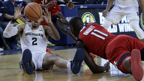Rutgers forward Eugene Omoruyi (11) and Michigan guard Jordan Poole (2) chase the loose ball during the first half of an NCAA college basketball game, Sunday, Jan. 21, 2018, in Ann Arbor, Mich. (AP Photo/Carlos Osorio)