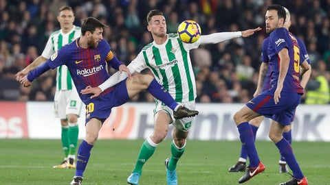 Barcelona's Messi, left, and Betis' Fabian, centre, fight for the ball during La Liga soccer match between Barcelona and Betis at the Villamarin stadium, in Seville, Spain on Sunday, Jan. 21, 2018. (AP Photo/Miguel Morenatti)