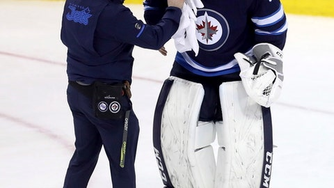 Winnipeg Jets goalie Connor Hellebuyck (37) is tended to after getting a stick to the eye from teammate Josh Morrissey during a play in front of the goal during the third period of the team's NHL hockey game against the Vancouver Canucks in Winnipeg, Manitoba, Sunday, Jan. 21, 2018. (Trevor Hagan/The Canadian Press via AP)