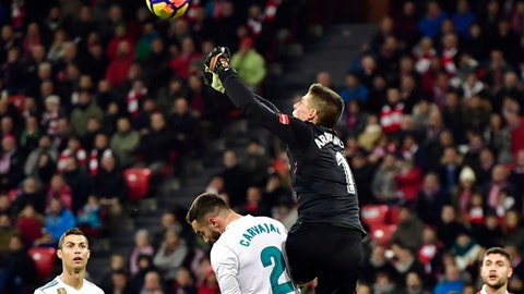 """FILE - In this Saturday, Dec. 2, 2017 file photo, Athletic Bilbao's goalkeeper Kepa Arrizabalaga, top, pushes the ball beside Real Madrid's Daniel Carvajal during their Spanish La Liga soccer match at San Mames stadium, in Bilbao, northern Spain. Athletic Bilbao has said on Monday, Jan. 22, 2018 it has extended the contract of young goalkeeper Kepa Arrizabalaga until June 2025, ending speculation about his move to Real Madrid. The 23-year-old Kepa admitted he had offers to leave Athletic, but decided to stay at the club he considers his """"home."""" (AP Photo/Alvaro Barrientos, file)"""