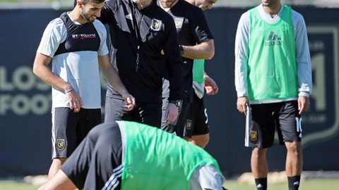 Head coach Bob Bradley, second from left, talks with Diego Rossi, left, with Carlos Vela at far right during the introduction of players and coaches at the first training camp of the Los Angeles Football Club soccer team on the campus of UCLA in Los Angeles, Monday, Jan. 22, 2018. (AP Photo/Reed Saxon)