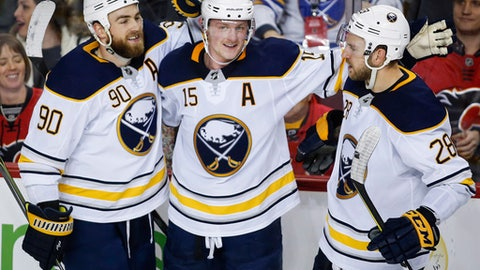 Buffalo Sabres' S Jack Eichel, center, celebrates his game-winning goal during overtime period NHL hockey action against the Calgary Flames in Calgary, Monday, Jan. 22, 2018. (Jeff McIntosh/The Canadian Press via AP)