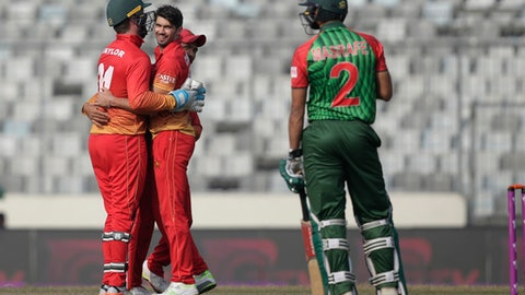 Zimbabwe's captain Graeme Cremer, second left, celebrate with his teammate Sikandar Raza, second right, and wicketkeeper Brendan Taylor, left, the dismissal of Bangladesh's captain Mashrafe Mortaza, right, during the Tri-Nation one-day international cricket series in Dhaka, Bangladesh, Tuesday, Jan. 23, 2018. (AP Photo/A.M. Ahad)