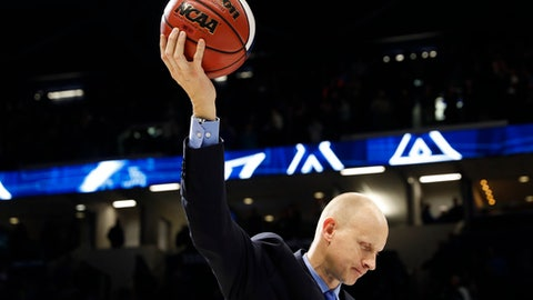 FILE - In this Wednesday, Jan. 17, 2018, file photo, Xavier head coach Chris Mack holds a commemorative game ball after becoming the winningest coach in Xavier history after an NCAA college basketball game against St. John's, in Cincinnati. Xavier and Cincinnati are as close as could be when it comes to geography and basketball. Only 2 1/2 miles apart on the map, they're separated by only one spot in the Top 10. It's quite a season for hoops in the Queen City. (AP Photo/John Minchillo, File)