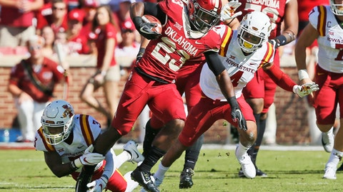 Oklahoma running back Abdul Adams (23) evades a tackle by Iowa State defensive back Reggie Wilkerson (3) during an NCAA college football game in Norman, Okla., Saturday, Oct. 7, 2017. (AP Photo/Sue Ogrocki)