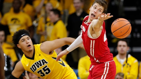 Wisconsin forward Ethan Happ tries to steal the ball from Iowa forward Cordell Pemsl, left, during the second half of an NCAA college basketball game Tuesday, Jan. 23, 2018, in Iowa City, Iowa. (AP Photo/Charlie Neibergall)