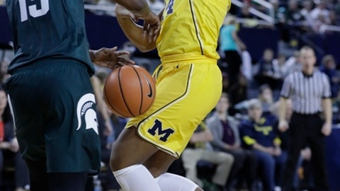 Michigan State forward Victoria Gaines (15) strips the ball away from Michigan guard Akienreh Johnson (14) during the second half of an NCAA college basketball game, Tuesday, Jan. 23, 2018, in Ann Arbor, Mich. (AP Photo/Carlos Osorio)