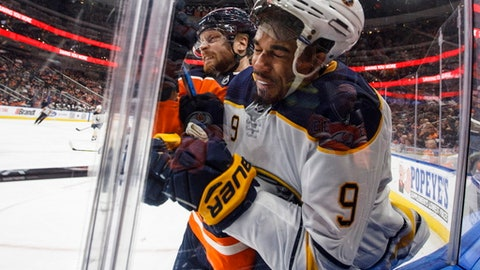 Buffalo Sabres left wing Evander Kane (9) is checked by Edmonton Oilers defenseman Adam Larsson during the third period of an NHL hockey game Tuesday, Jan. 23, 2018, in Edmonton, Alberta. (Jason Franson/The Canadian Press via AP)