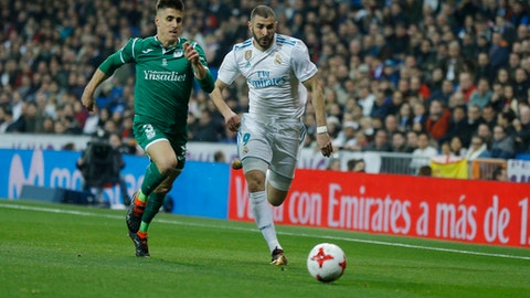 Real Madrid's Karim Benzema, right, battles for the ball with Leganes' Unai Bustinza during the Spanish Copa del Rey quarterfinal second leg soccer match between Real Madrid and Leganes at the Santiago Bernabeu stadium in Madrid, Wednesday, Jan. 24, 2018. (AP Photo/Francisco Seco)