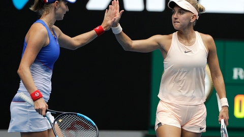 Russia's Ekaterina Makarova, left, and Elena Vesnina celebrate a point win against Hungary's Timea Babos and France's Kristina Mladenovic during the women's doubles final at the Australian Open tennis championships in Melbourne, Australia, Friday, Jan. 26, 2018. (AP Photo/Dita Alangkara)