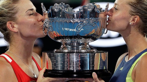 Hungary's Timea Babos, left, and partner France's Kristina Mladenovic kiss their trophy after they defeated Russia's Ekaterina Makarova and Elena Vesnina in the women's doubles final at the Australian Open tennis championships in Melbourne, Australia, Friday, Jan. 26, 2018. (AP Photo/Dita Alangkara)