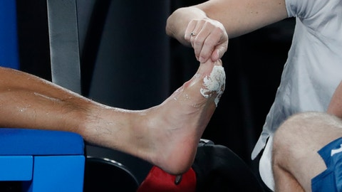 Medical staff attend to the foot of South Korea's Hyeon Chung during his semifinal against Switzerland's Roger Federer at the Australian Open tennis championships in Melbourne, Australia, Friday, Jan. 26, 2018. (AP Photo/Vincent Thian)