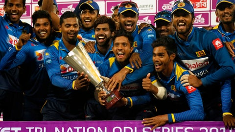 Sri Lanka's players pose for a group photo while celebrating with the trophy after winning the final match against Bangladesh of the Tri-Nation one-day international cricket series in Dhaka, Bangladesh, Saturday, Jan. 27, 2018. (AP Photo/A.M. Ahad)