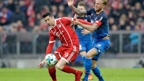 Bayern's Robert Lewandowski, left, and Hoffenheim's Kevin Vogt challenge for the ball during the German Soccer Bundesliga match between FC Bayern Munich and TSG 1899 Hoffenheim in Munich, Germany, Saturday, Jan. 27, 2018. (AP Photo/Matthias Schrader)