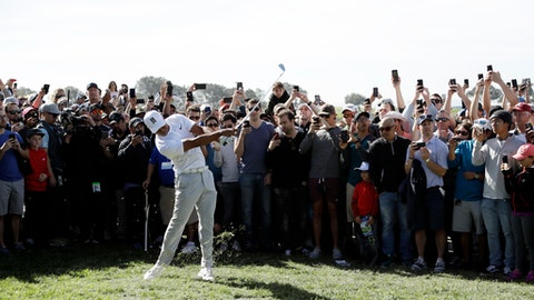 Fans record with cell phones as Tiger Woods hits from the rough on the 14th hole of the South Course at Torrey Pines Golf Course during the third round of the Farmers Insurance Open golf tournament, Saturday, Jan. 27, 2018, in San Diego. (AP Photo/Gregory Bull)