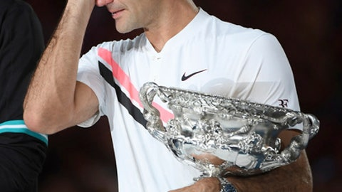 Switzerland's Roger Federer wipes a tear away as he holds his trophy after defeating Croatia's Marin Cilic in the men's singles final at the Australian Open tennis championships in Melbourne, Australia, Sunday, Jan. 28, 2018. (AP Photo/Andy Brownbill)