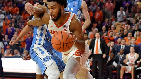 Clemson's Gabe DeVoe, center, dribbles after grabbing a rebound with seconds left on the clock, while defended by North Carolina's Joel Berry II, left, and Luke Maye during the second half of an NCAA college basketball game Tuesday, Jan. 30, 2018, in Clemson, S.C. Clemson won 82-78. (AP Photo/Richard Shiro)