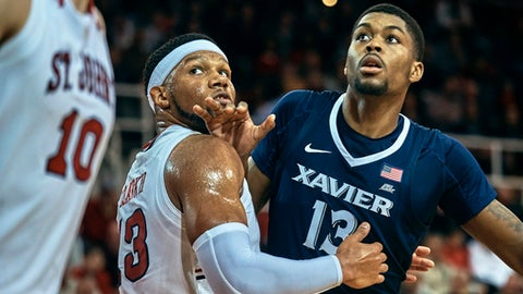 Xavier's Naji Marshall, right, fight for the ball with St. John's Marvin Clark II, center, during the first half of an NCAA college basketball game at Carnesecca Arena in the Queens borough of New York, Tuesday, Jan. 30, 2018. (AP Photo/Andres Kudacki)