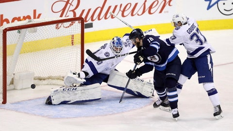 Winnipeg Jets' Bryan Little (18) fires the puck past Tampa Bay Lightning's goaltender Louis Domingue (70) with Yanni Gourde (37) trying to check him during the third period of an NHL hockey game, Tuesday, Jan. 30, 2018 in Winnipeg, Manitoba. (Trevor Hagan/The Canadian Press via AP)