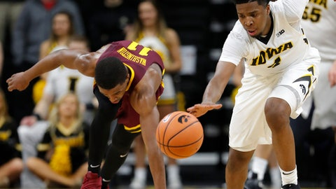 Iowa guard Isaiah Moss, right, steals the ball from Minnesota guard Isaiah Washington, left, during the second half of an NCAA college basketball game, Tuesday, Jan. 30, 2018, in Iowa City, Iowa. Iowa won 94-80. (AP Photo/Charlie Neibergall)