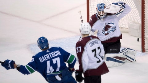 Vancouver Canucks' Sven Baertschi, left, begins to celebrates his overtime goal against Vancouver Canucks goalie Jonathan Bernier, next to Avalanche left wing J.T. Compher (37) in an NHL hockey game Tuesday, Jan. 30, 2018, in Vancouver, British Columbia. (Jonathan Hayward/The Canadian Press via AP)