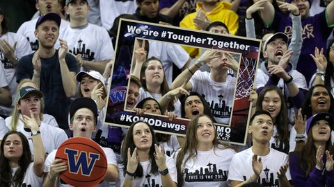 In this Sunday, Jan. 28, 2018 photo, fans in the student section cheer as they hold a promotional frame with a #TougherTogether motivational hashtag on it during an NCAA college basketball game against Washington State in Seattle. The phrase is one of many posted on gym walls during practice by Washington head coach Mike Hopkins, and one of the most surprising stories in college basketball is what Hopkins is doing in his first season at Washington and how the Huskies are in the conversation for an NCAA bid entering February. (AP Photo/Ted S. Warren)