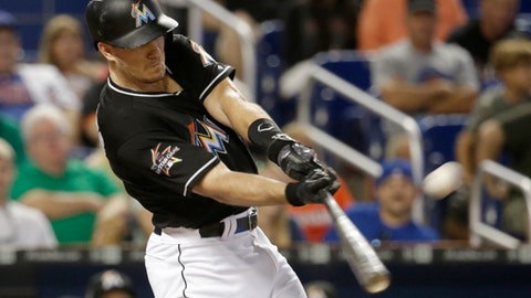 FILE - In this June 24, 2017, file photo, Miami Marlins' J.T. Realmuto hits a three-run home run during the first inning of a baseball game against the Chicago Cubs in Miami. Realmuto, among the Marlins who could be traded as part of the team's payroll purge under new chief executive Derek Jeter, went to salary arbitration with Miami on Thursday, Jan. 31, 2018, and asked that he be given a raise to $3.5 million instead of $2.9 million. (AP Photo/Lynne Sladky, File)