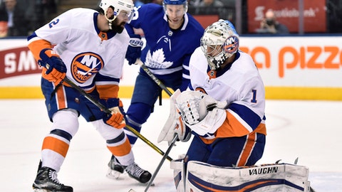 New York Islanders goaltender Thomas Greiss (1) makes a save as Islanders defenseman Nick Leddy (2) and Toronto Maple Leafs center Dominic Moore (20) look for a rebound during the second period of an NHL hockey game Wednesday, Jan. 31, 2018, in Toronto. (Frank Gunn/The Canadian Press via AP)