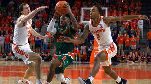 Jan 13, 2018; Clemson, SC, USA; Miami Hurricanes guard Chris Lykes (2) drives to the basket while being defended by Clemson Tigers forward David Skara (24) and guard Marcquise Reed (2) during the first half at Littlejohn Coliseum. Mandatory Credit: Joshua S. Kelly-USA TODAY Sports