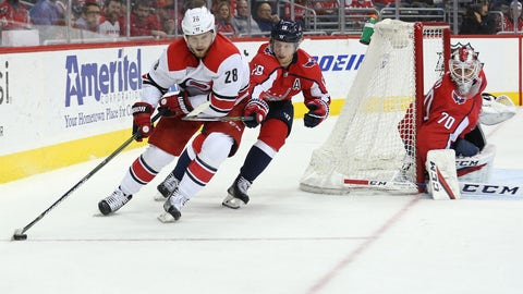 Jan 11, 2018; Washington, DC, USA; Carolina Hurricanes center Elias Lindholm (28) skates with the puck behind Washington Capitals goaltender Braden Holtby (70) as Capitals center Nicklas Backstrom (19) defends in the first period at Capital One Arena. Mandatory Credit: Geoff Burke-USA TODAY Sports